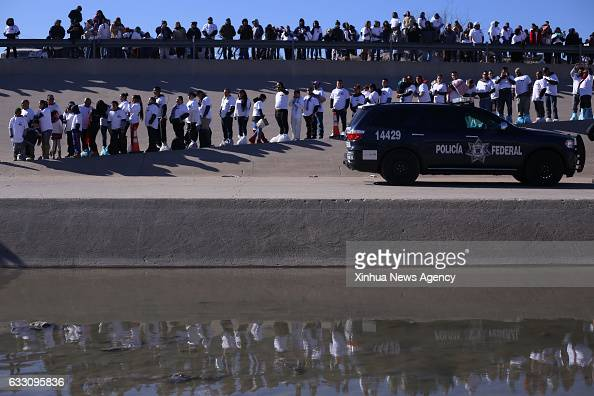 People stand in line to cross the river Rio Bravo to participate in the event called 'Hugs not Walls' in Ciudad Juarez in the state of Chihuahua...
