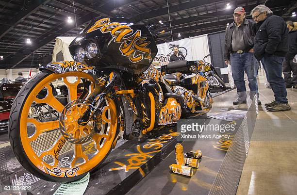 Visitors watch a tuned motorcycle during the 2017 North American International Motorcycle Supershow in Toronto Canada on Jan 7 2017 As one of the...