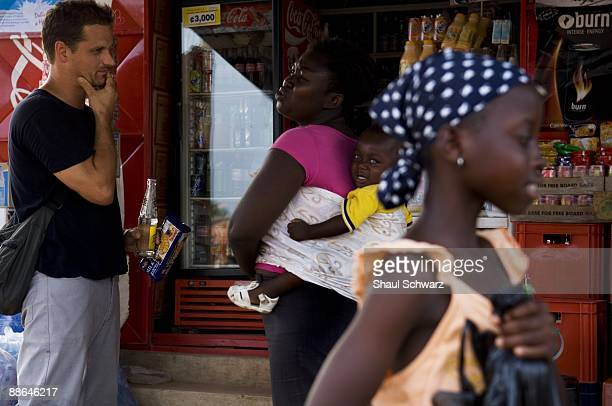 Jan Chipchase a Human Behavioral Researcher for Nokia talks to a local shop owner as he walks throe a local market in the Capitol city of Accra...
