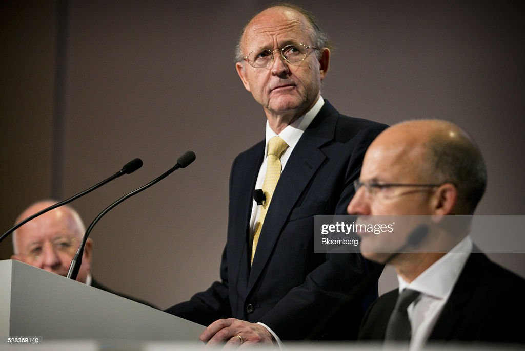 Jan du Plessis, chairman of Rio Tinto Group, center, pauses during a speech as Samuel 'Sam' Walsh, outgoing chief executive officer, left, and Tim Paine, joint secretary, right, listen during the company's annual general meeting in Brisbane, Australia, on Thursday, May 5, 2016. Rio Tinto Group, the second-largest mining company, reaffirmed its goal to raise annual iron ore output in Australia to 360 million metric tons amid forecast growth demand in Asia. Photographer: Patrick Hamilton/Bloomberg via Getty Images