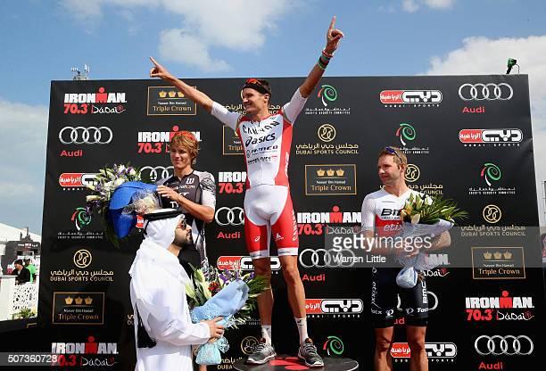 Jan Frodeno of Germany celebrates on the podium as Sheikh Mansoor Bin Mohammed Bin Rashid looks on after the Men's IRONMAN 703 Dubai on January 29...