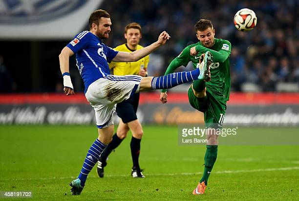 Jan Kirchhoff of Schalke 04 challenges Daniel Baier of Augsburg during the Bundesliga match between FC Schalke 04 and FC Augsburg at Veltins Arena on...
