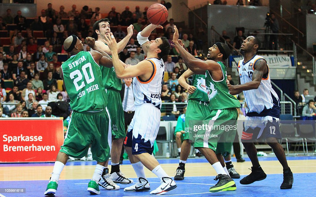 Jan Lipke of Bremerhaven and John Redder Bynum and Philip Zwiener and Dru Joyce of Trier battle for the ball during the Basketball Bundesliga match...