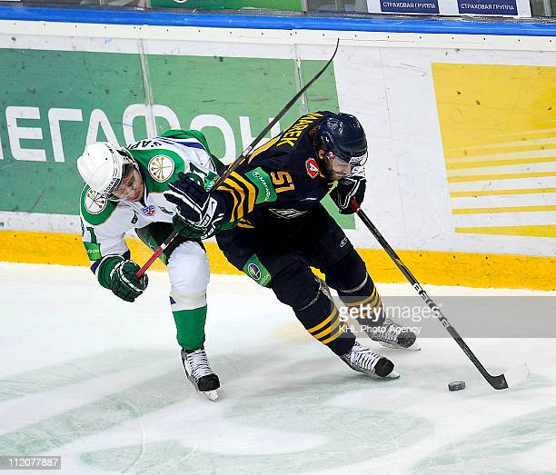 Jan Marek of the Atlant Mytishchi skates with the puck under pressure from Oleg Saprykin of the Salavat Yulaev Ufa during the Game Three of the 2011...