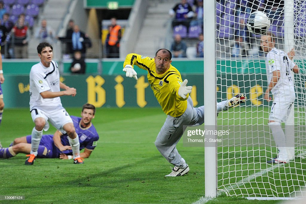 Jan Mauersberger (2nd L) scores his teams second goal against goalkeeper Gabor Kiraly (2nd R) of Munich during the first round match of the DFB Cup between VfL Osnabrueck and TSV 1860 Muenchen at the osnatel Arena on July 29, 2011 in Osnabruck, Germany.