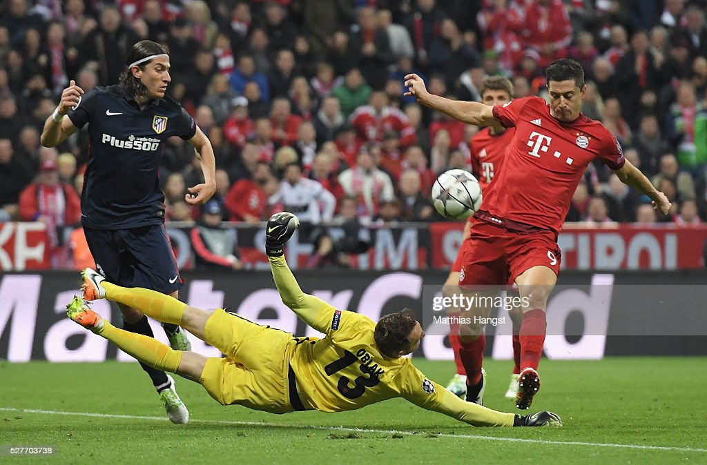 Jan Oblak of Atletico Madrid dives to block Robert Lewandowski of Bayern Munich during UEFA Champions League semi final second leg match between FC Bayern Muenchen and Club Atletico de Madrid at Allianz Arena on May 3, 2016 in Munich, Germany.
