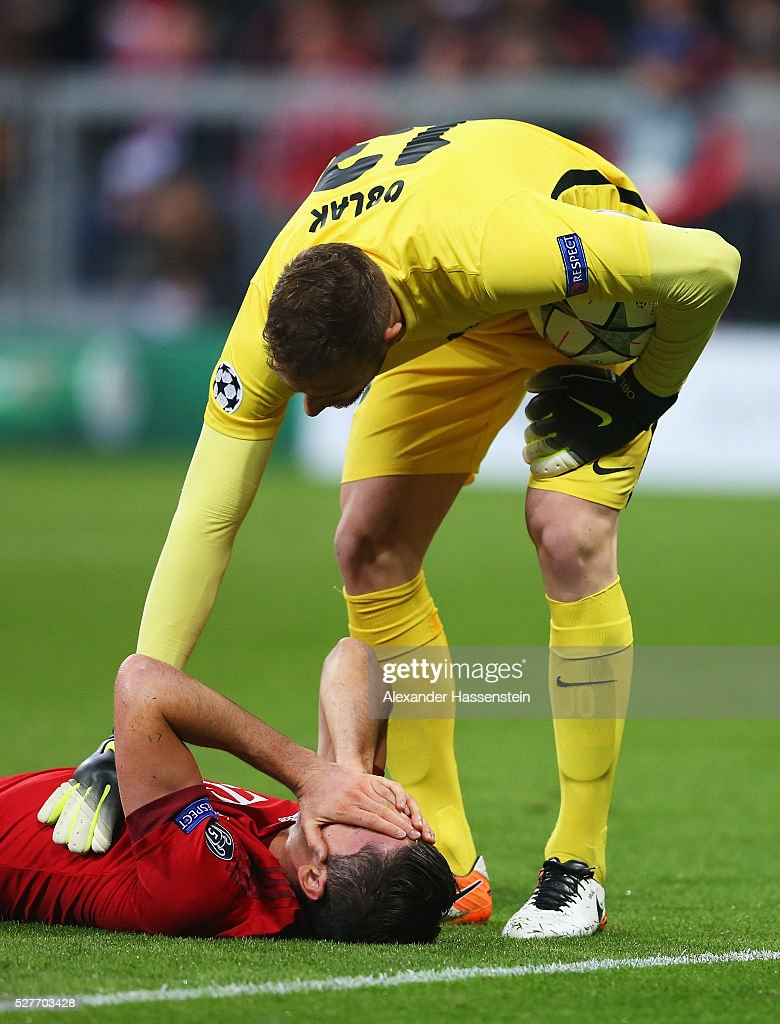Jan Oblak of Atletico Madrid stands over an injured Robert Lewandowski of Bayern Munich during UEFA Champions League semi final second leg match between FC Bayern Muenchen and Club Atletico de Madrid at Allianz Arena on May 3, 2016 in Munich, Germany.