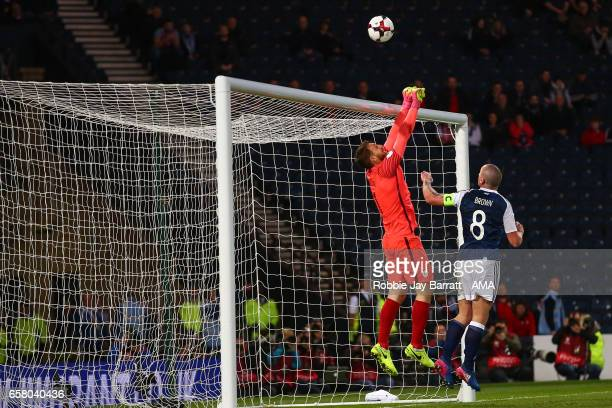 Jan Oblak of Slovenia punches the ball over the bar under pressure from Scott Brown of Scotland during the FIFA 2018 World Cup Qualifier between...