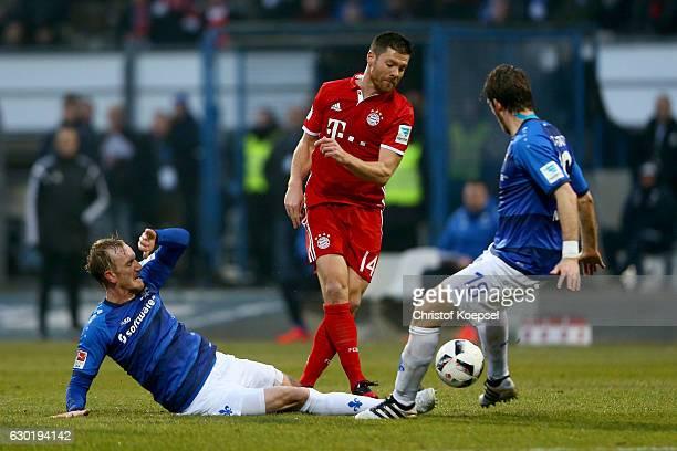 Jan Rosenthal of Darmstadt and Peter Niemeyer of Darmstadt challenge Xabi Alonso of Bayern Muenchen during the Bundesliga match between SV Darmstadt...