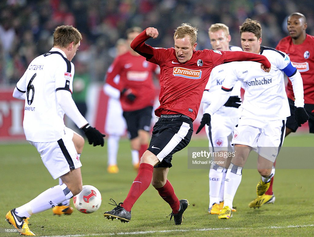 Jan Rosenthal of Freiburg fighting for ball against Bastian Oczipka (L) and Pirmin Schwegler (R) of Eintracht Frankfurt during the Bundesliga match between SC Freiburg and Eintracht Frankfurt at MAGE SOLAR Stadium on February 22, 2013 in Freiburg, Germany.