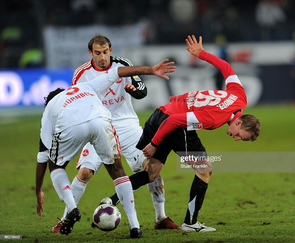 Jan Rosenthal of Hannover is challenged by Breno and Javier Pinola of Nuernberg during the Bundesliga match between Hannover 96 and FC Nuernberg at...