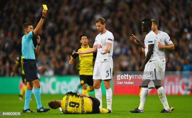 Jan Vertonghen of Tottenham Hotspur is shown a yellow card by referee Gianluca Rocchi as Andrey Yarmolenko of Borussia Dortmund reacts during the...