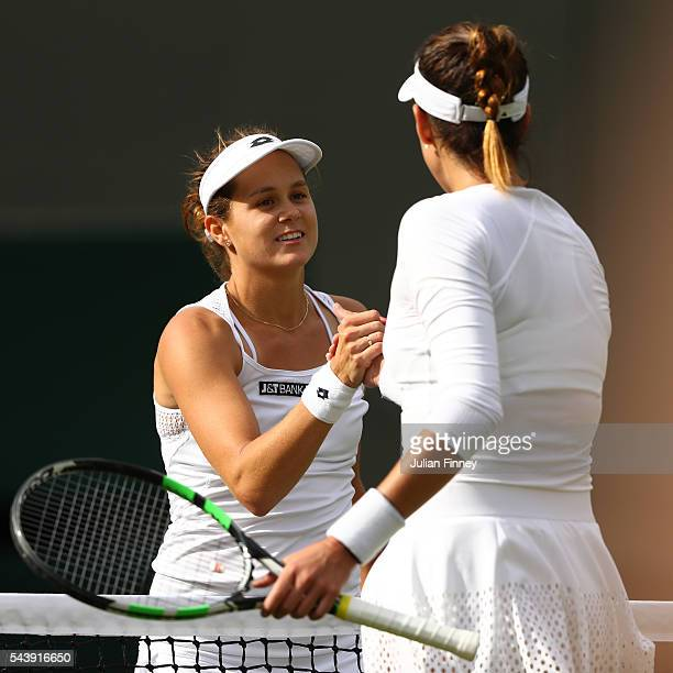 Jana Cepelova of Slovakia shakes hands with Gabrine Muguruza of Spain during the Ladies Singles second round match on day four of the Wimbledon Lawn...