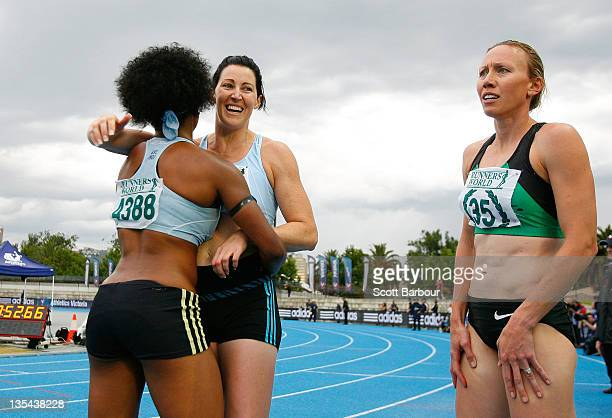 Jana Pittman of Glen Huntly is embraced by a team mate as Tamsyn Lewis of Sandringham looks on after the Victorian 4x400m Womens Final during the...