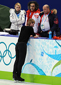 Jana Rudkovskaya the wife of Russia's Evgeny Plushenko and his coach Alexey Mishin look at the champion at the end of his performance in his Figure...