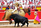 A Jandilla's bull charges a picador's horse during the fifth corrida of the San Fermin Festival in Pamplona on July 11 2016 The festival is a symbol...