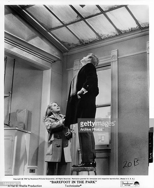 Jane Fonda and Robert Redford looking up towards the ceiling in a scene from the film 'Barefoot In The Park' 1967
