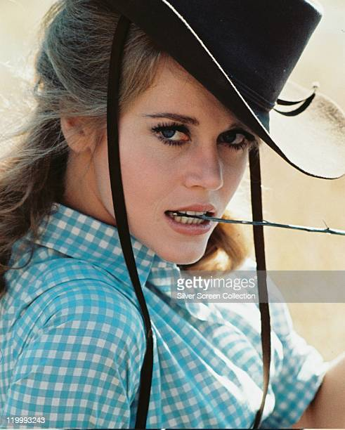 Jane Fonda US actress wearing a black cowboy hat and blue gingham shirt posing with a twig between her teeth in a publcity portrait issued for the...