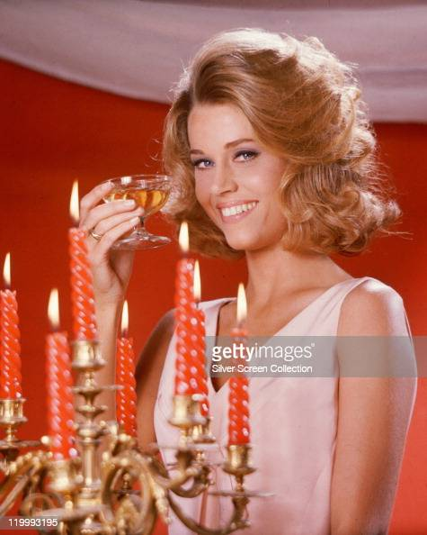 Jane Fonda US actress wearing a pink sleeveless top posing with a champagne coupe beside a candelabra with lit candles in a studio portrait against a...