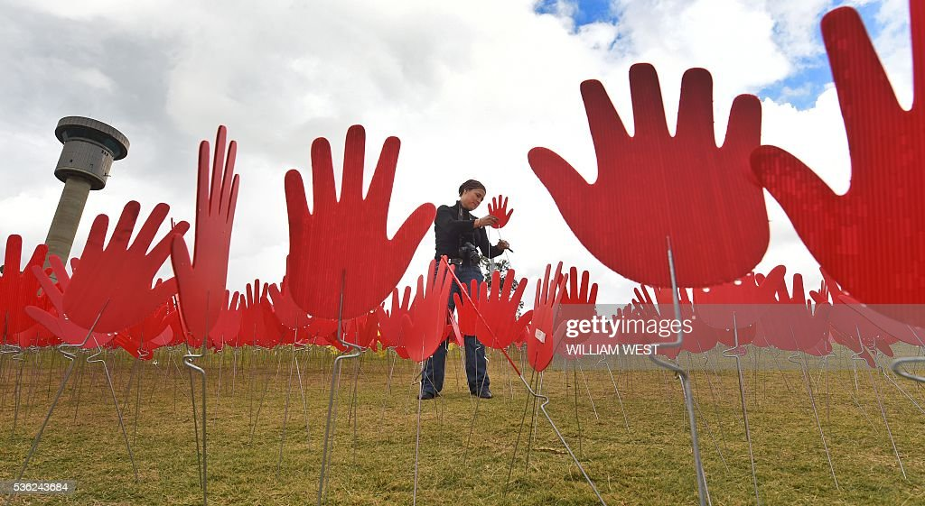 Jane Powles, national campaign manager for ANTAR, places hands in a huge art installation called 'Sea of Hands' which consists of thousands of hands in the colours of the Aboriginal flag red, yellow, black. Part of National Reconciliation Week 2016, the installation is for Australians to reflect on Australias national identity and the place of Aboriginal and Torres Strait Islander histories and cultures in the nations story. / AFP / WILLIAM