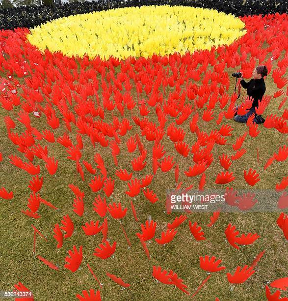 Jane Powles national campaign manager for ANTAR takes photos in a huge art installation called 'Sea of Hands' which consists of thousands of hands in...