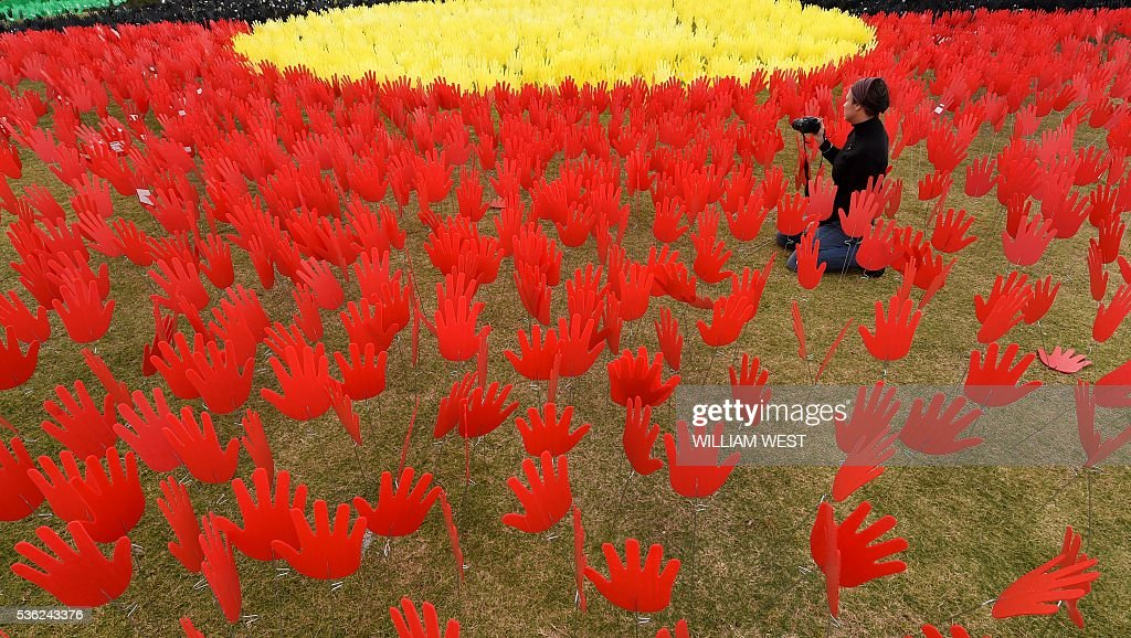 Jane Powles, national campaign manager for ANTAR, takes photos in a huge art installation called 'Sea of Hands' which consists of thousands of hands in the colours of the Aboriginal flag red, yellow, black. Part of National Reconciliation Week 2016, the installation is for Australians to reflect on Australias national identity and the place of Aboriginal and Torres Strait Islander histories and cultures in the nations story. / AFP / WILLIAM