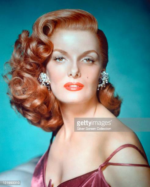 Jane Russell looking glamorous wearing a purple top with the shoulder strap slipped down over her left shoulder and a pair of pearl earrings circa...