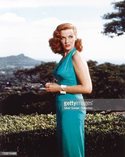Jane Russell US actress with red hair wearing a blue halterneck dress and a white bracelet circa 1955