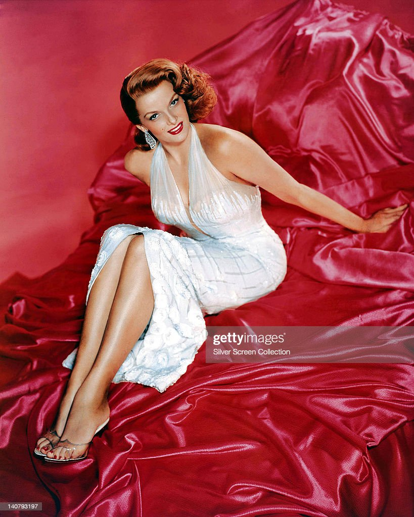 Jane Russell (1921-2011), wearing a white halterneck dress, and reclining on red silk sheets in a studio portrait, against a red background, circa 1945.
