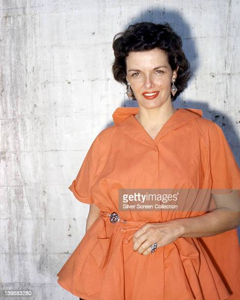 Jane Russell wearing an orange dress with large drop earrings in a studio portrait against a white background circa 1955