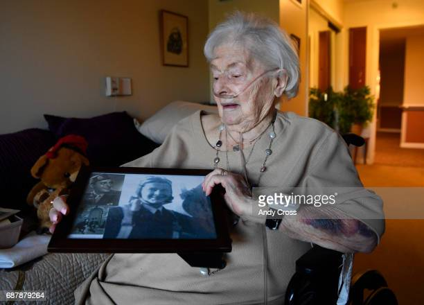 Jane Tedeschi holds a picture frame with WWII era pictures of herself and her husband Romolo Tedeschi upper right a WWII Bronze Star recipient at her...