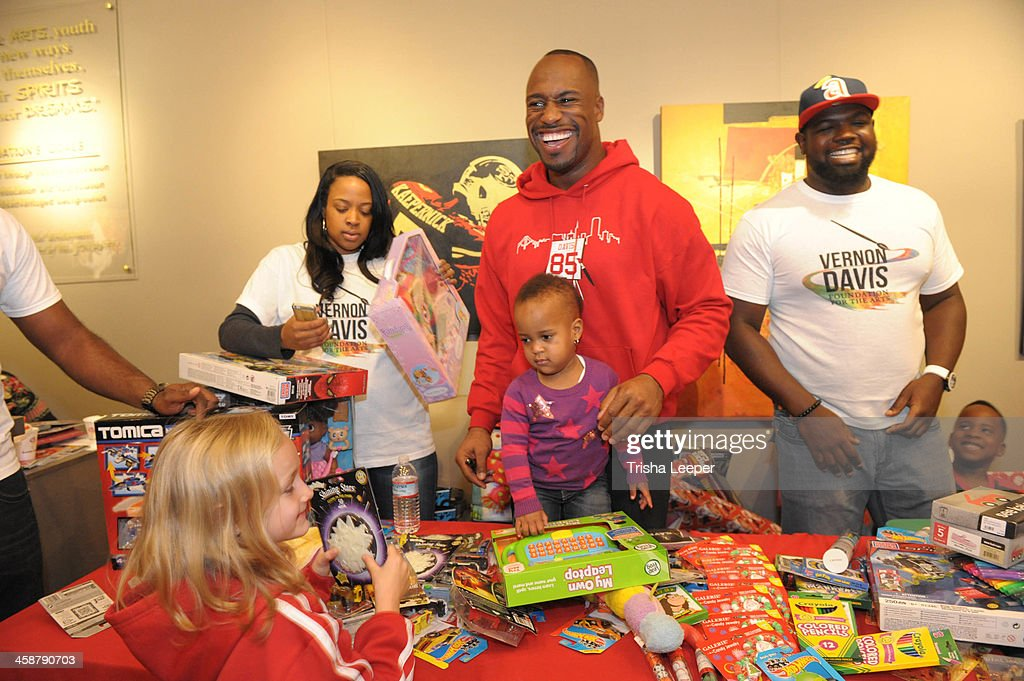 Janel Davis and <a gi-track='captionPersonalityLinkClicked' href=/galleries/search?phrase=Vernon+Davis&family=editorial&specificpeople=592553 ng-click='$event.stopPropagation()'>Vernon Davis</a> attends The <a gi-track='captionPersonalityLinkClicked' href=/galleries/search?phrase=Vernon+Davis&family=editorial&specificpeople=592553 ng-click='$event.stopPropagation()'>Vernon Davis</a> Foundation For The Arts Christmas Toy Give Away at <a gi-track='captionPersonalityLinkClicked' href=/galleries/search?phrase=Vernon+Davis&family=editorial&specificpeople=592553 ng-click='$event.stopPropagation()'>Vernon Davis</a> Art Gallery on December 21, 2013 in San Jose, California.