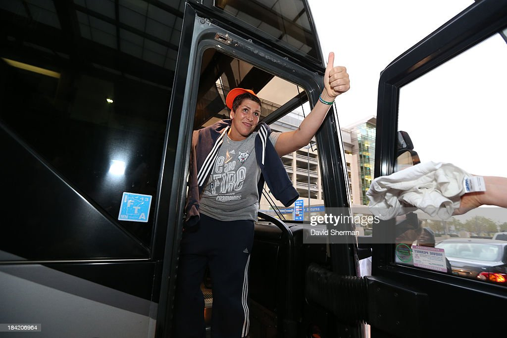 Janel McCarville of the 2013 WNBA Champion Minnesota Lynx gives a thumbs-up to the crowd while getting on the team bus on October 11, 2013 at Minneapolis-St. Paul International Airport in St. Paul, Minnesota.