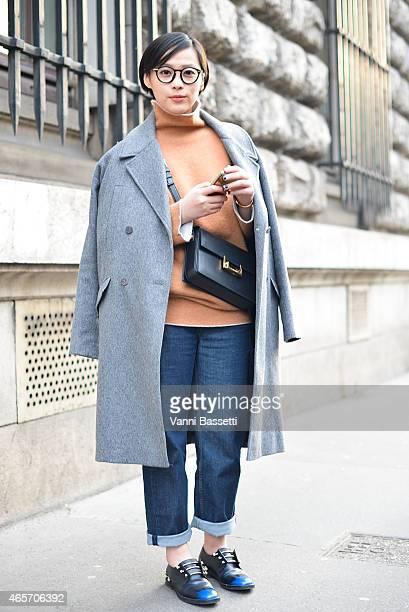 Janet Tseng poses wearing a Designer Remix coat Jil Sander jumper Balenciaga pants Coliac shoes and YSL bag on Day 7 of Paris Fashion Week Womenswear...