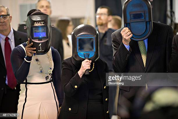 Janet Yellen chair of the US Federal Reserve center and Charles Plosser chairman of the Federal Reserve Bank of Chicago right hold welding masks over...
