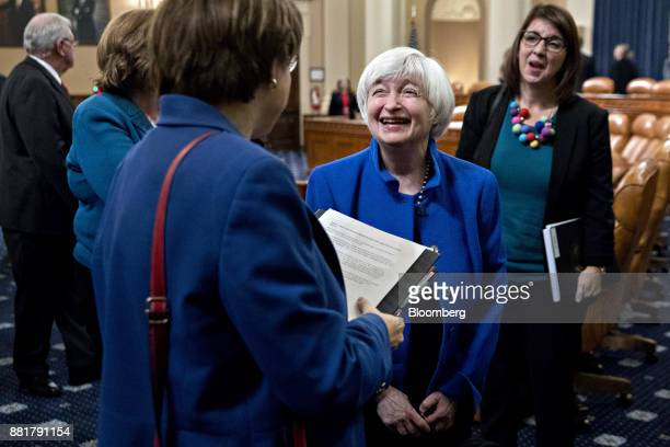 Janet Yellen chair of the US Federal Reserve center smiles while talking to Senator Amy Klobuchar a Democrat from Minnesota left after a Joint...