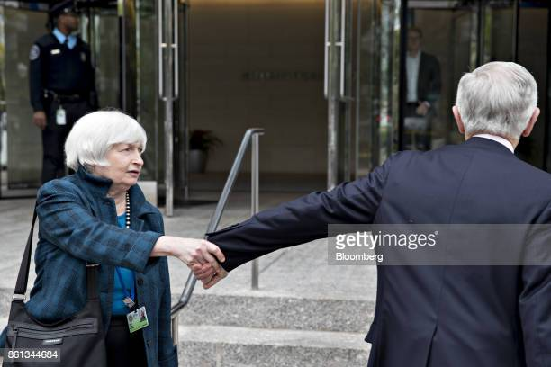 Janet Yellen chair of the US Federal Reserve left and Stanley Fischer former vice chairman of the US Federal Reserve hold hands while saying goodbye...