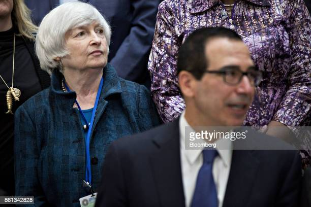 Janet Yellen chair of the US Federal Reserve left stands next to Steven Mnuchin US Treasury secretary during an International Monetary Fund governors...