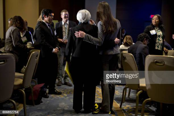 Janet Yellen chair of the US Federal Reserve left takes photograph with an attendee before speaking at the Federal Reserve System Community...