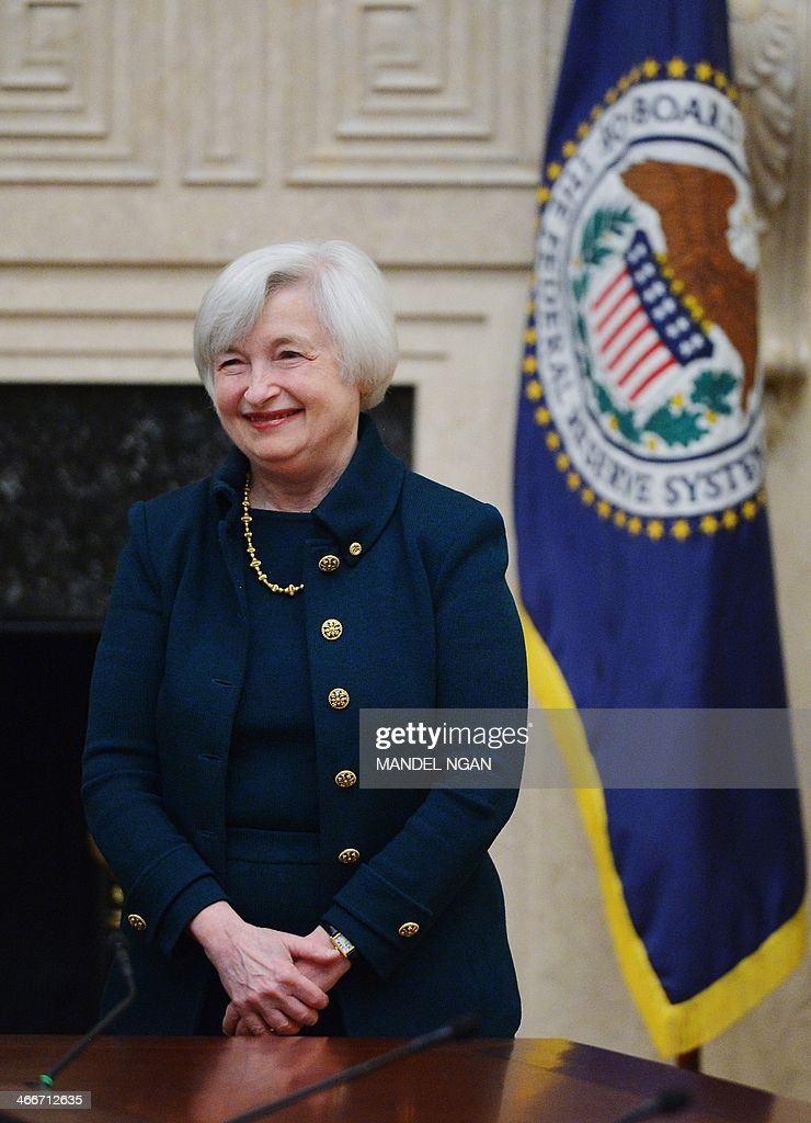 Janet Yellen smiles after taking the oath of office as Chair of the Board of Governors of the Federal Reserve System on February 3, 2014 at the Eccles Building in Washington, DC. Respected economist Janet Yellen was sworn in Monday as the first woman chair of the Federal Reserve, taking on the burden of winding down the Fed's stimulus without spurring more turmoil. Yellen inherits the mantle of the world's most powerful central banker from Ben Bernanke, who guided the US and the global financial system through its deepest crisis since the 1930s during his eight years in the job. AFP PHOTO/Mandel NGAN