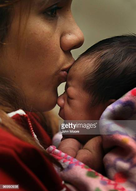 Janeth Fernandez kisses her daughter Sarah during a newborn checkup at a community health center on February 23 2010 in Aurora Colorado The Metro...