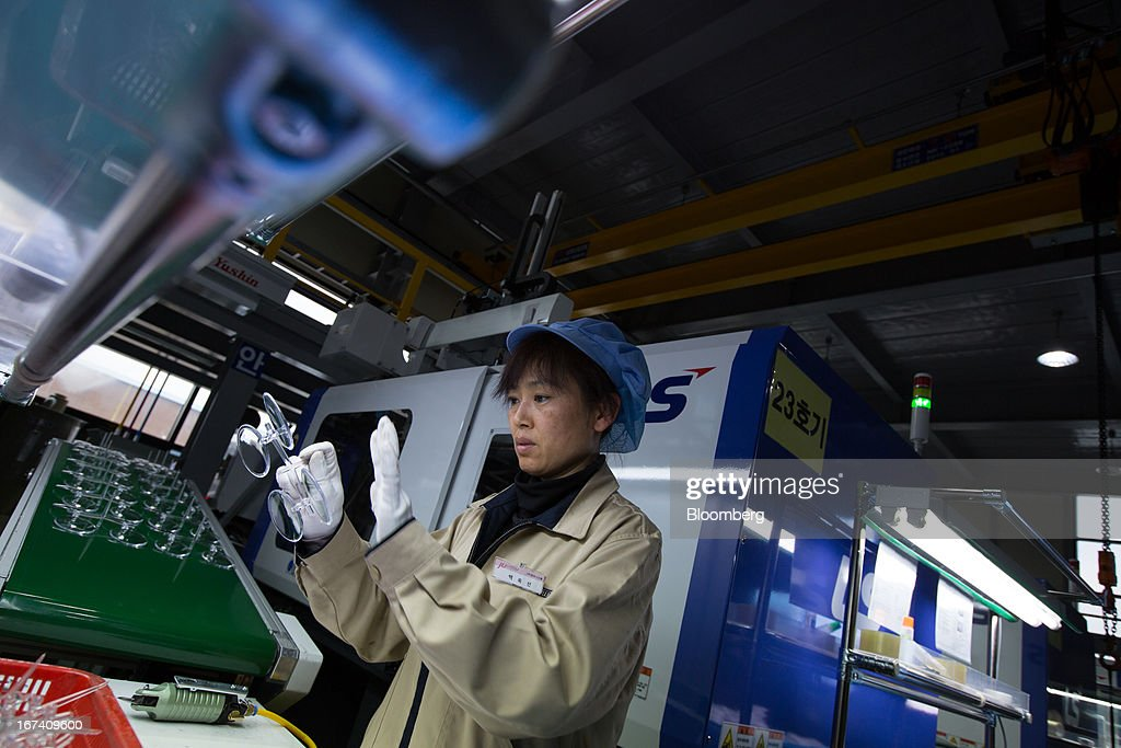 A Jangup System Co. employee inspects caps for compacts on the production line for manufacturing cosmetic containers at the company's factory in Yongin, South Korea, on Wednesday, April 24, 2013. South Korea's economy grew the most in two years in the first quarter as the government front-loaded spending and exporters weathered the slide in the yen that aids rivals in Japan. Photographer: SeongJoon Cho/Bloomberg via Getty Images