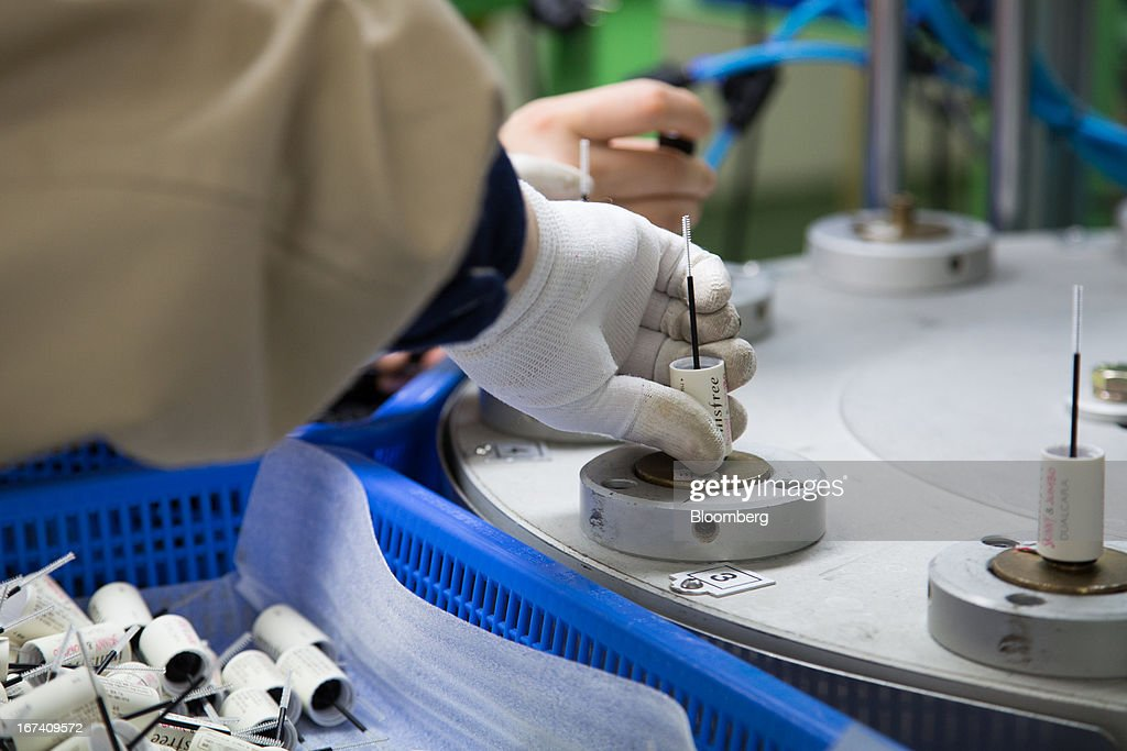 A Jangup System Co. employee puts an Amorepacific Corp.'s Innisfree branded Skinny & Jumbo Dual Cara mascara container and brush into an assembly machine on the production line for manufacturing cosmetics containers at the company's factory in Yongin, South Korea, on Wednesday, April 24, 2013. South Korea's economy grew the most in two years in the first quarter as the government front-loaded spending and exporters weathered the slide in the yen that aids rivals in Japan. Photographer: SeongJoon Cho/Bloomberg via Getty Images