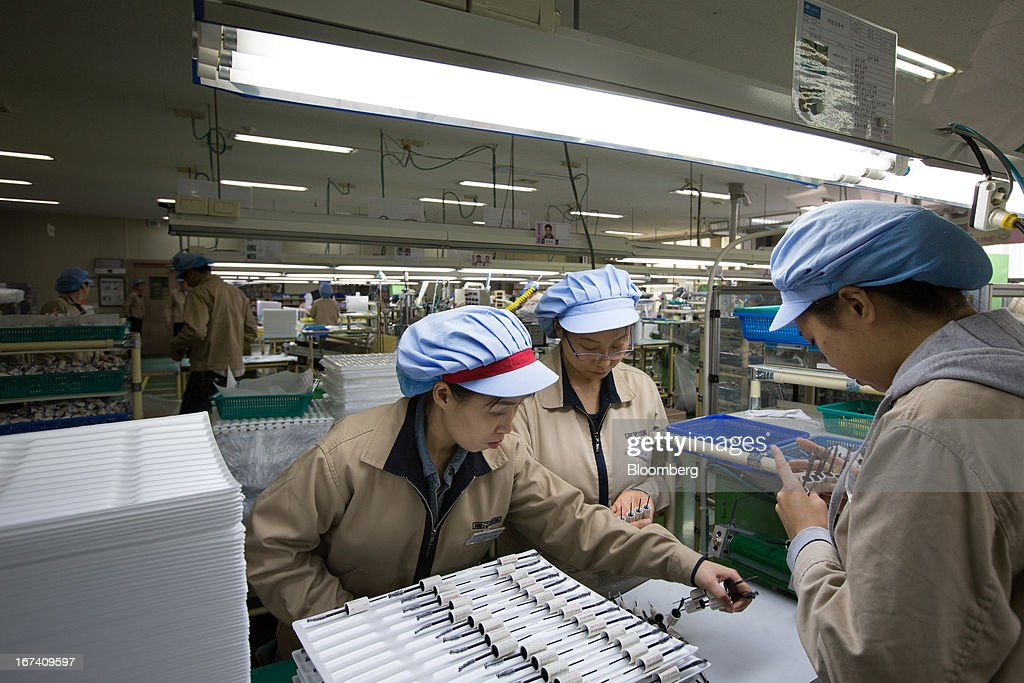Jangup System Co. employees inspect Amorepacific Corp.'s Innisfree branded Skinny & Jumbo Dual Cara mascara containers and brushes on the production line for manufacturing cosmetics containers at the company's factory in Yongin, South Korea, on Wednesday, April 24, 2013. South Korea's economy grew the most in two years in the first quarter as the government front-loaded spending and exporters weathered the slide in the yen that aids rivals in Japan. Photographer: SeongJoon Cho/Bloomberg via Getty Images