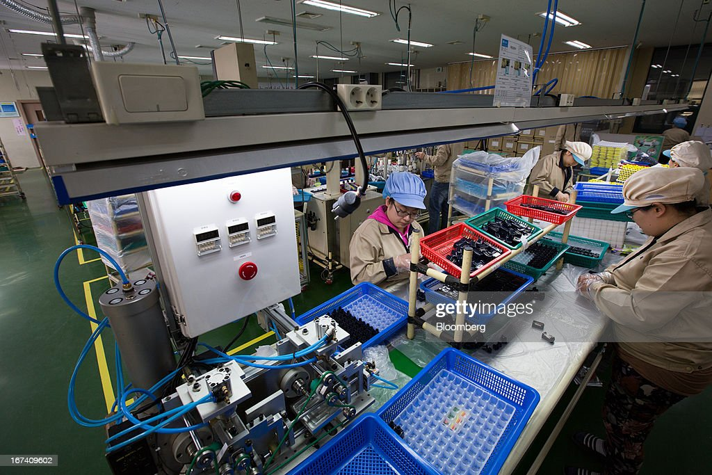 Jangup System Co. employees work on the production line for manufacturing cosmetic containers at the company's factory in Yongin, South Korea, on Wednesday, April 24, 2013. South Korea's economy grew the most in two years in the first quarter as the government front-loaded spending and exporters weathered the slide in the yen that aids rivals in Japan. Photographer: SeongJoon Cho/Bloomberg via Getty Images