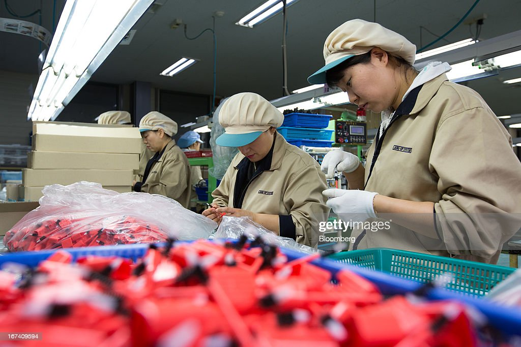Jangup System Co. employees work on the production line manufacturing cosmetics containers at the company's factory in Yongin, South Korea, on Wednesday, April 24, 2013. South Korea's economy grew the most in two years in the first quarter as the government front-loaded spending and exporters weathered the slide in the yen that aids rivals in Japan. Photographer: SeongJoon Cho/Bloomberg via Getty Images