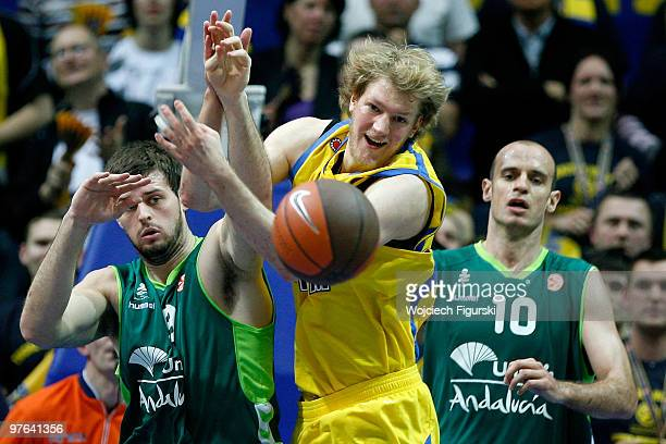 JanHendrick Jagla #14 of Asseco Prokom competes with Joel Freeland #19 and Carlos Jimenez #10 of Unicaja Malaga in action during the Euroleague...