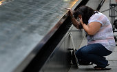 Janice Lynch of Queens New York pauses at the inscription of her friend Patricia Massani's name at the North Pool for the memorial observances held...