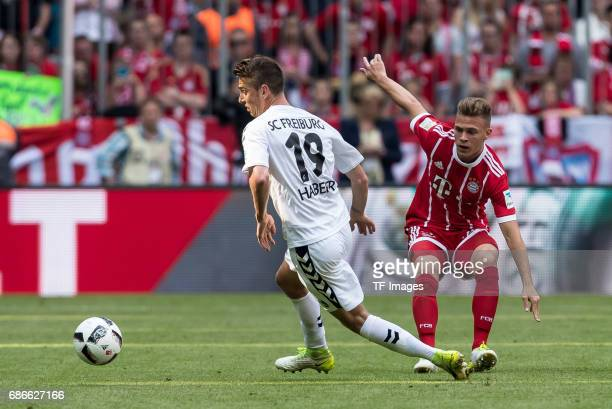 Janik Haberer of Freiburg and Joshua Kimmich of Bayern Muenchen battle for the ball during the Bundesliga match between Bayern Muenchen and SC...