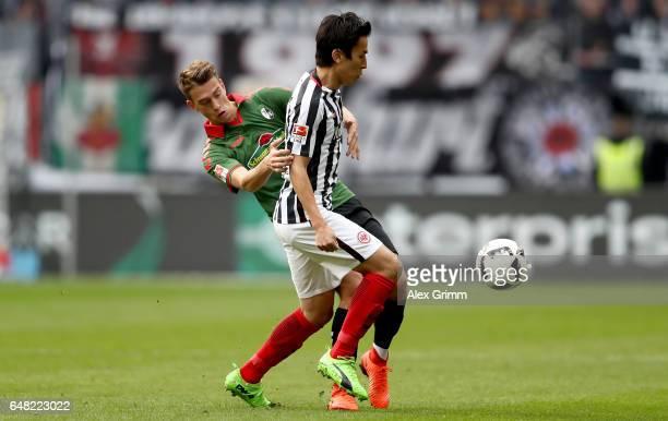 Janik Haberer of Freiburg challenges Makoto Hasebe of Frankfurt during the Bundesliga match between Eintracht Frankfurt and SC Freiburg at...